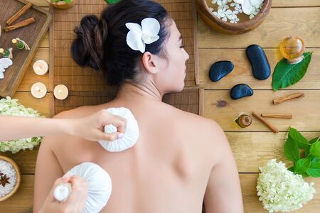 Top view young woman is getting thai massage, therapy. Master hands are massaging client with herbal bags. Brunette girl is lying on couch in light spa ayurveda salon. Relax and health care concept. Stock Photo