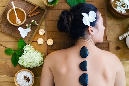 Top view young woman is getting hot massage, therapy. Basalt black stones are placed along spine of relaxed female. Brunette girl is lying on couch in spa ayurveda salon. Relax and health care concept
