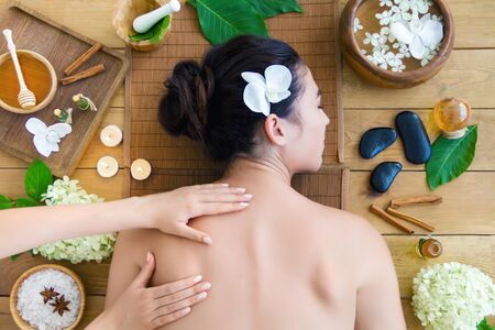 Top view young woman is getting thai massage, therapy. Master hands are massaging kneading back of client. Brunette girl is lying on couch in light spa ayurveda salon. Relax and health care concept.