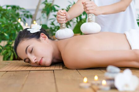 Young pleased woman is getting thai massage, therapy. Female master is massaging client with herbal bags. Brunette girl is lying on couch in light spa ayurveda salon. Relax and health care concept. Reklamní fotografie