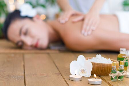 Closeup burning candles, bottles with aroma oil, bowl with salt. Young pleased woman is getting thai massage, therapy. Brunette girl is lying on couch in spa ayurveda salon. Relax and health care.