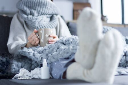 Sick girl in scarf and knitted socks is sitting in bed sofa wrapped in grey blanket. Ill woman is drinking tea and taking pills medications. Home treatment. Winter cold and flu concept.