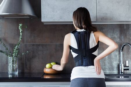 Brunette girl is standing in kitchen and holding hand on back. Young woman dressed orthopedic bandage for relieve spine stress, correct posture, restore after injury. Treatment of spinal diseases Stock fotó