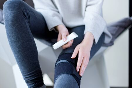 Closeup female leg dressed in knee brace to help promote recovery of bones, muscles, ligaments. Woman is feeling pain in joints after injury and going to use ointment. Arthritis and meniscus diseases.