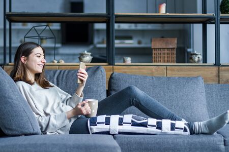 Smiling brunette girl with broken leg is sitting on couch sofa, resting and drinking tea at home. Injured young woman wearing supporting compression bandage for trauma. Sick leave concept.