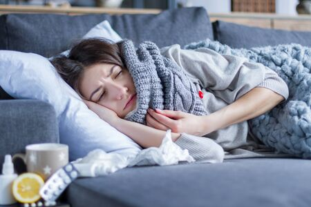 Sick exhausted girl in scarf is lying in bed wrapped in blanket. Young woman with fever and headache is measuring temperature with thermometer, treated at home. Winter cold and flu concept.