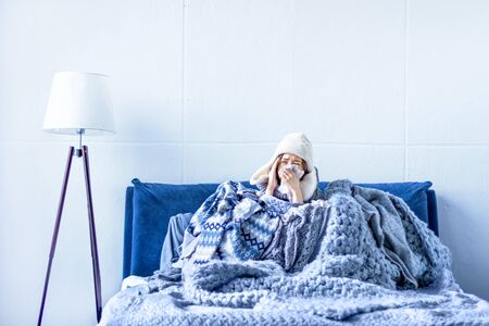 Sick exhausted girl in white warm hat wrapped herself in scarves and blankets is sitting in bed. Young woman with runny nose, fever and headache is treated at home. Winter cold and flu concept.