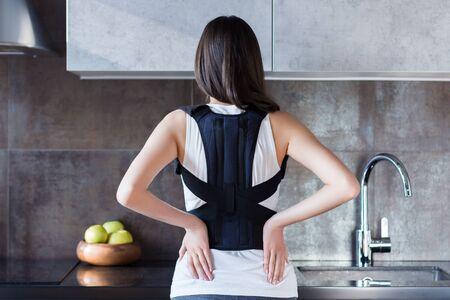 Brünettes Mädchen steht in der Küche und hält die Hand auf dem Rücken. Junge Frau kleidete orthopädische Bandage zur Entlastung der Wirbelsäule, zur richtigen Haltung, zur Wiederherstellung nach einer Verletzung. Behandlung von Wirbelsäulenerkrankungen Standard-Bild