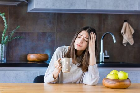 Brunette girl is sitting at table in kitchen and holding hand on head temple. Young woman is feeling bad. Sudden attack of migraine and headache. Effects of stress, passive, unhealthy lifestyle.