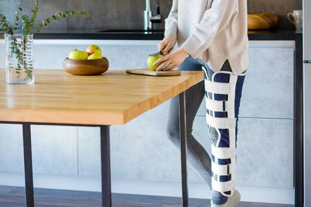 Girl with broken leg is standing in kitchen and cooking. Injured woman wearing supporting compression bandage for trauma to help promote recovery of bones, muscles, ligaments. Orthopedic diseases. Stock fotó