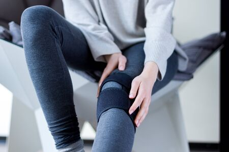 Closeup female leg in grey leggings dressed in knee brace to help promote recovery of bones, muscles, ligaments. Woman is feeling pain in joints after injury. Arthritis and meniscus diseases concept. Stockfoto