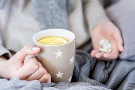 Closeup female hands are holding cup of tea with lemon and analgesic, antipyretic healing pills, vitamins. Woman wrapped on grey blanket is treated at home. Winter cold and flu concept.