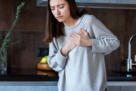 Young woman in grey clothes is holding hands on breast. Brunette girl is feeling bad. Sudden heart attack, myocardial infarction at home. Effect of stress and unhealthy lifestyle concept. Stock fotó