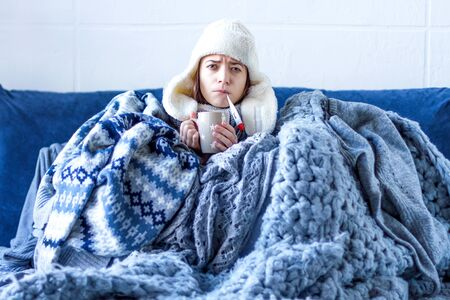 Sick exhausted girl in white warm hat wrapped herself in scarves and blankets is sitting in bed. Young woman with fever is drinking tea and measuring temperature with thermometer. Winter cold and flu. Stockfoto