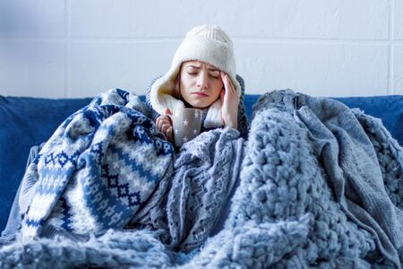 Sick exhausted girl in white warm hat wrapped herself in scarves and blankets is sitting in bed. Young woman with fever and headache is treated, drinking tea. Winter cold and flu concept. Stockfoto