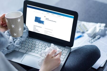 Closeup female hands are holding laptop and cup of tea. Ill girl is sitting at sofa and working remotely. Young woman having snot is treated at home, took sick leave. Winter cold and flu concept.