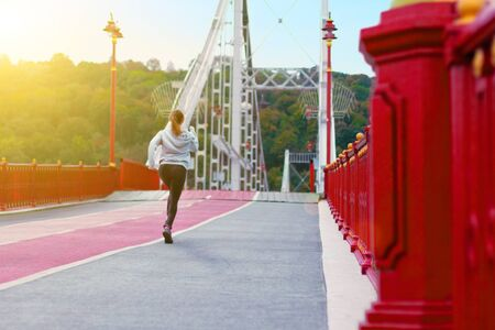 Back view of athletic girl, in black grey sportswear, is running marathon on pedestrian urban bridge at city. Young woman is doing morning exercises. Sporty and healthy lifestyle concept. Stockfoto