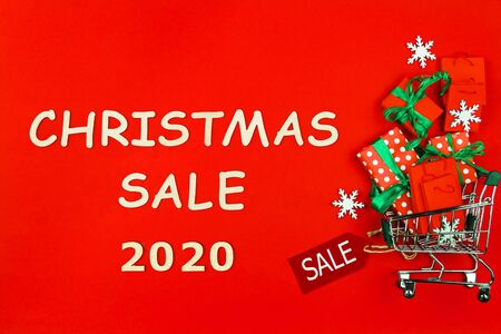 Small trolley, mini shopping cart full of presents and packages. Gift boxes are packed in decorative paper and green ribbons on red background. Inscription christmas sale 2020. New year fair market.