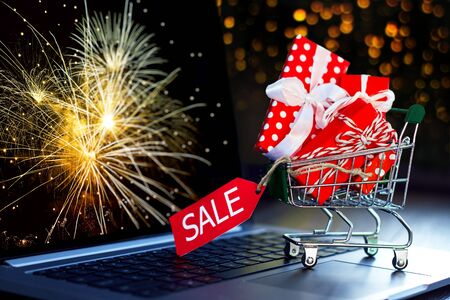 Small green trolley, mini pushcart filled with bright gift boxes are on laptop computer with salute on display. Gold bokeh on background. Online shopping concept. New year, christmas sale.