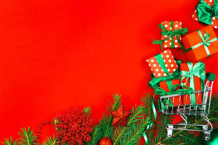 Small trolley, mini shopping cart full of presents. Gift boxes in wrapping paper with green ribbons, decorated christmas tree branch on red background. New year fair, market, sale concept.  Stockfoto
