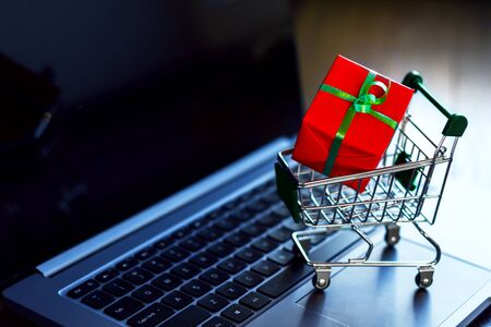 Gift box wrapped in red paper with green ribbon in small trolley, mini pushcart, cart are on laptop computer. Online shopping concept. Black friday sale. New year, christmas fair, market.  Stockfoto