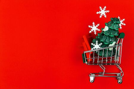 Small green trolley, mini cart filled with shopping bags, packages and christmas tree on red background. Preparing for celebration, buying gifts. Black friday sale. New year fair, market concept.