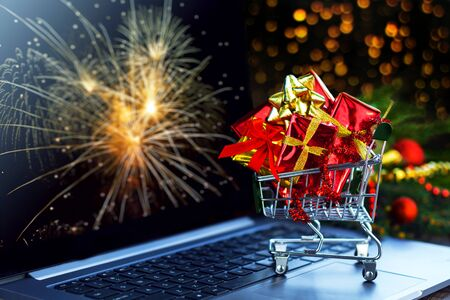 Small green trolley, mini cart filled with bright gift boxes are on laptop computer. Decorated christmas tree branch on background. Online shopping concept. Black friday sale. New year fair.   Stockfoto