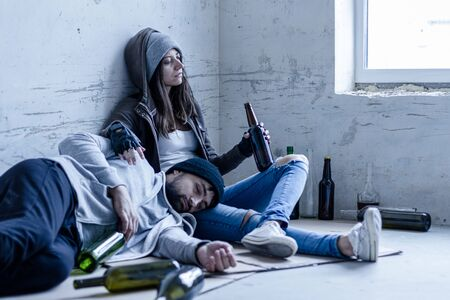 Homeless bums young man and woman are lying on cardboard on floor in abandoned building. Drunkard guy is sleeping and girl is drinking beer. Alcohol abuse addiction and street life concept.