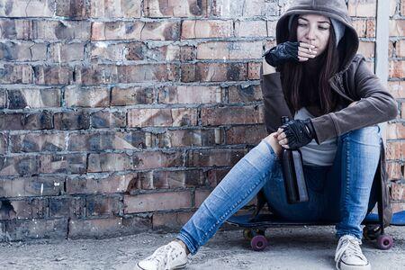 Mujer joven con capucha está sentada en patineta y sosteniendo un cigarrillo humeante y una botella de cerveza. Adolescente sin hogar está bebiendo y fumando en un edificio abandonado. Escoria del concepto de sociedad.