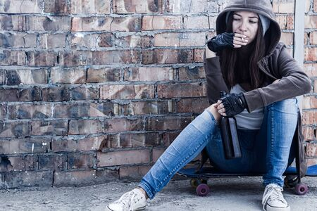 Young woman in hood is sitting on skateboard and holding smoldering cigarette and bottle of beer. Homeless teenage girl is drinking and smoking in abandoned building. Dregs of society concept.