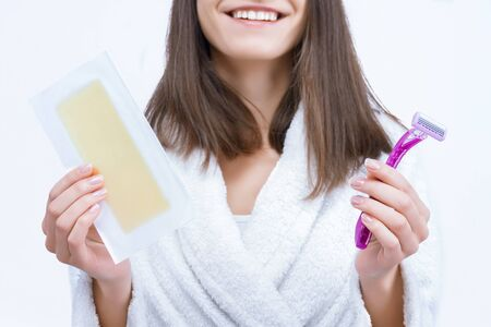 Portrait of young woman is choosing unwanted hair removal tool. Girl is holding disposable razor and wax stripe, going to shave depilate legs, armpits, bikini zone. Personal care and hygiene product