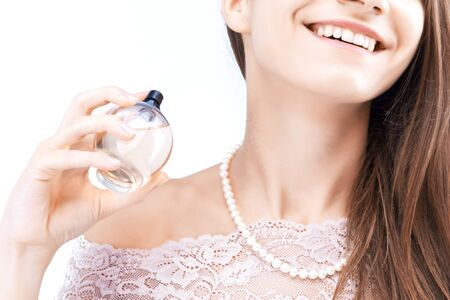 Closeup of female hand is holding little bottle with fragrant perfume. Young woman is spraying cosmetic deodorant to neck. Girl is preparing for event. Personal hygiene and care, morning routine.