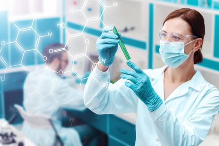 Portrait of woman doctor is researching test tube with chemical liquid on background of laboratory. Scientists are working, conducting experiments with plants. Biologist, biotechnologist workplace.