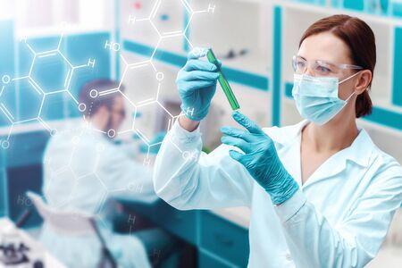Retrato de mujer médico está investigando tubo de ensayo con líquido químico en el fondo del laboratorio. Los científicos están trabajando, realizando experimentos con plantas. Biólogo, biotecnólogo en el lugar de trabajo.
