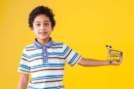 Curly pretty dark skinned boy in blue striped t-shirt is holding little cart for buying goods, products. Black cute child is smiling on orange yellow background. Shopping and sale concept. Stock Photo