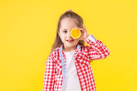 Pretty beautiful fair haired girl in checkered pink shirt is smiling on bright yellow background. Fashionable cute child is holding half of orange in front of eye. Emotional portrait concept.