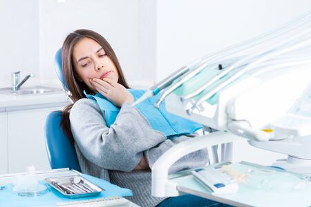 Upset sad woman is holding hand on her cheek, teeth, sitting in chair in dental office, clinic. Female is feeling pain and toothache, waiting for doctor dentist examining. Dentistry concept.
