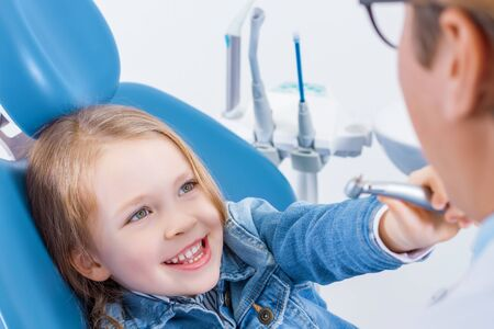 Little girl is sitting in dental chair, holding in hand tool. Orthodontist is preparing for examination child teeth. Friendly relationships between doctor and patient. Visiting dentist with children.