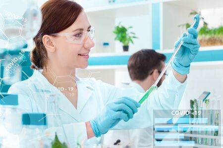 Young woman pharmacist virologist is working on vaccine in test tube in laboratory. Process of inventing cure against virus SARS-CoV-2, 2019-nCoV. Coronavirus Covid-19 pandemic, epidemic concept.