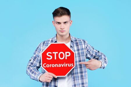 Young man is holding warning red sign symbol stop coronavirus. Virus SARS-CoV-2, 2019-nCoV that leads to infectious respiratory illness disease Covid-19, pneumonia. Pandemic epidemic concept.