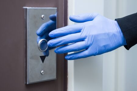Closeup male hand in medical gloves is pressing elevator call button. Virus SARS-CoV-2 , 2019-nCoV are in air around, on surfaces. Prevention and hygiene rules during pandemic of coronavirus covid-19