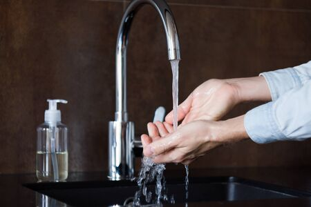 Closeup man is washing hands with soap for 20-30 seconds to prevent virus SARS-CoV-2, 2019-nCoV infection, that leads to respiratory illness. Personal hygiene and care. Coronavirus covid-19 pandemic.