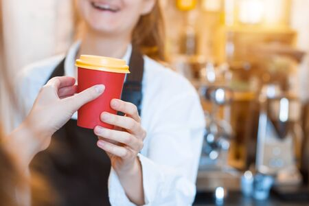Closeup female hands are holding paper disposable cup of coffee. Woman prepared, brewed espresso, americano, latte cappuccino in cafe. Barista is giving order to client. Take away, to go concept.