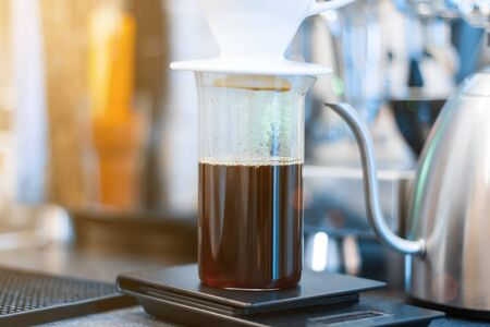 Closeup process of preparing, brewing coffee. Barista is making drink with hand drip method, pouring water on ground with filter, using special set of kettle and glass capacity. Hot beverages concept.