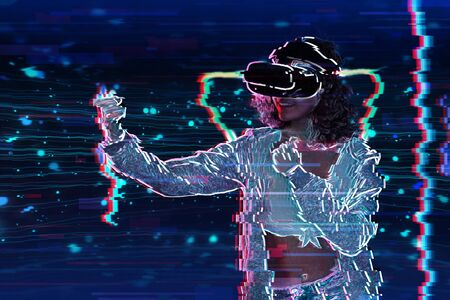 Teenage curly girl is playing in virtual reality game club. Smiling young woman in VR glasses is gaming with holograms, fighting in simulator. Entertainment and leisure concept. Modern technologies. Archivio Fotografico