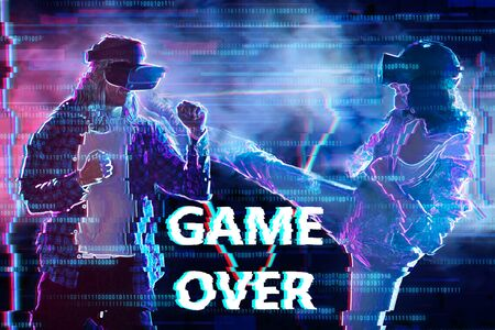 Girl and boy are playing in virtual reality club. Young woman and man in VR glasses are gaming. Opponents are fighting in simulator. Inscription game over. Entertainment and leisure concept.