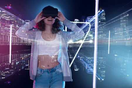 Teenage curly girl is playing in game club. Smiling surprised young woman in VR glasses is watching 3d virtual city tour in simulator. Entertainment and leisure concept. Modern technologies. Stock Photo