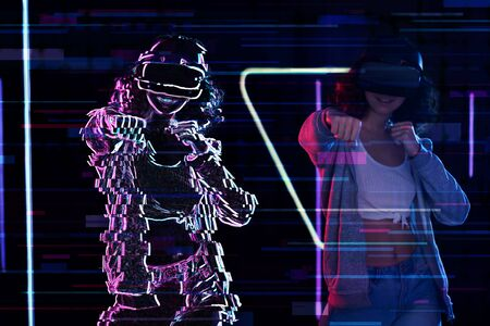 Teenage curly girl is playing in virtual reality game club. Smiling young woman in VR glasses is gaming with holograms, fighting in simulator. Entertainment and leisure concept. Modern technologies. Stock Photo