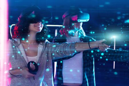 Boy and girl are playing in virtual reality game club. Young woman and man in VR glasses are gaming with holograms using wireless controllers. Entertainment and leisure concept. Modern technologies. Stock Photo