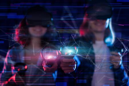 Closeup hands are holding wireless controllers. Boy and girl are playing in virtual reality game club. Young friends in VR glasses are gaming. Entertainment and leisure concept. Modern technologies. Stock Photo